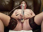 Ginger-haired cougar using vibrator on her couch at home